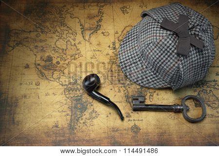 Deerstalker Sherlock Hat, Vintage Key, Smoking Pipe On Old Map.