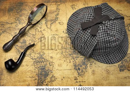 Deerstalker Hat Vintage Magnifier And Smoking Pipe On The Old World Map Background. Overhead View. Investigation Concept.