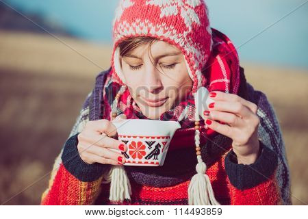 Nomad woman drinking hot beverages outdoor. Lifestyle concept.