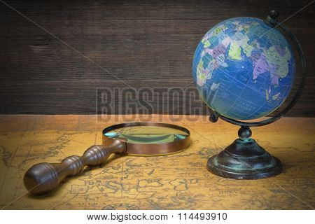 World Globe  And Magnifier On The Old Map
