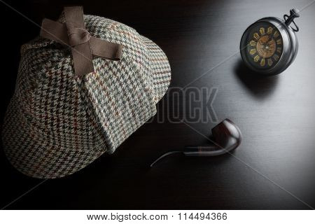 Deerstalker Hat Vintage Clock And Smoking Pipe On The Black Table Background. Overhead View. Investigation Concept.