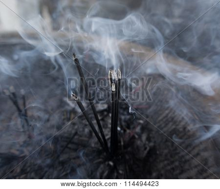Incense sticks burning in the temple's bowl