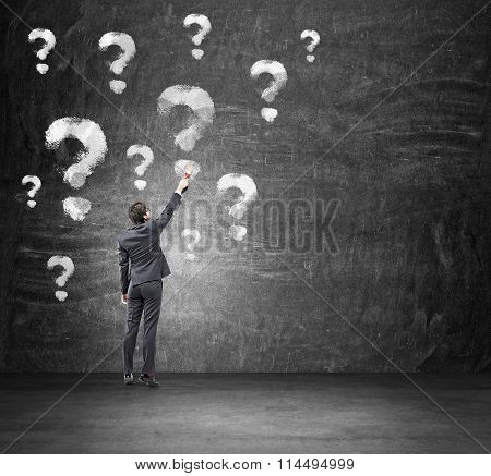 Young Man Painting Question Marks