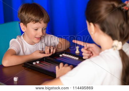 Boy And Girl Playing A Board Game Called Backgammon