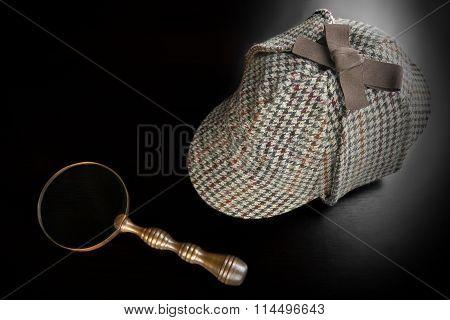 Sherlock Deerstalker Hat,   And Vintage  Magnifying Glass On Black Table