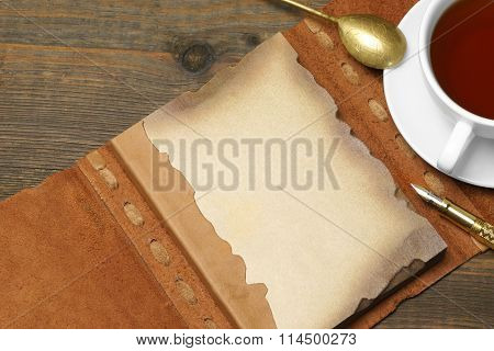 Opened Vintage Notebook With Blank Brown Page, Pen, Teacup, Spoon