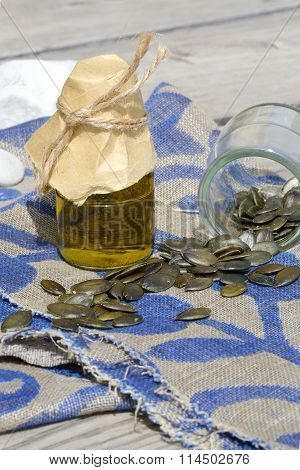 Pumpkin green seeds oil in a glass bottle on a decorative sackcloth