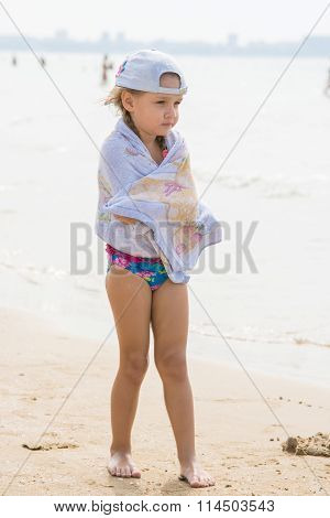 Frozen Girl Standing On The Beach Wrapped In A Towel