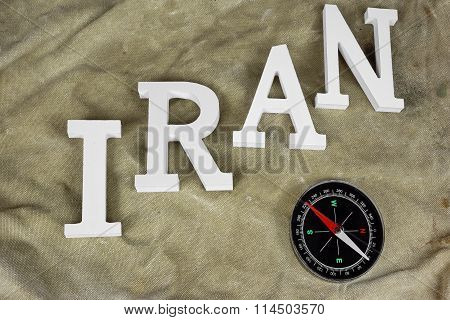 Sign Iran And Compass On The Weathered Backpack Background