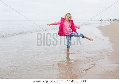 Three Year Old Girl Having Fun Stood On One Leg On The Beach