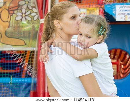 Young Mother Hugs And Kisses Tired Three-year Daughter Had A Soft Gaming Room