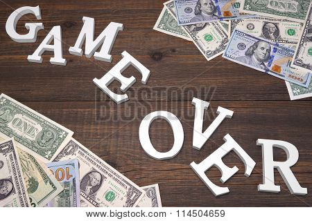 Sign Game Over And Dollars Bills On The Wood Background