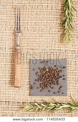 Black Pepper On Dark Plates With Rosemary And Antique Fork