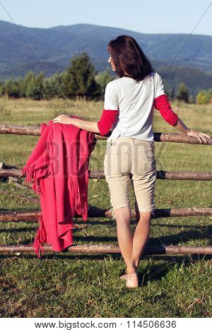 The Thoughtful Girl Leaning On A Wooden Fence, Turns Around And Looks Afar