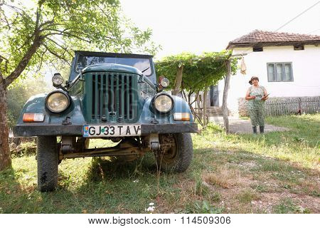 PADES, ROMANIA - JULY 27:  an old M461 ARO - the romanian jeep - in a rural fund of Cerna Sat, on background a peasant woman in front of her farmhouse. Shot in 2016