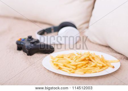 Plateful of fries and gaming devices on the sofa.