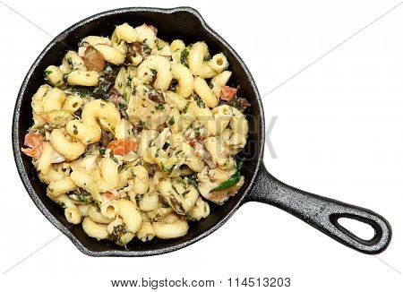 Tuscan Chicken Pasta in Cast Iron Skillet isolated over white.
