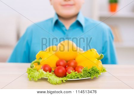 Smiling kid in front of plate filled with veggies.