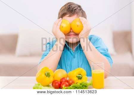 Chubby kid playing with oranges.