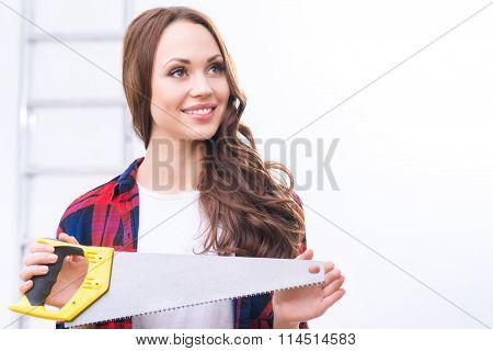 Girl holding a saw and looking up.