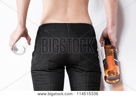 The woman in jeans with a bottle of whiskey on a white background.