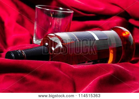 A bottle of whiskey and a glass on a red background