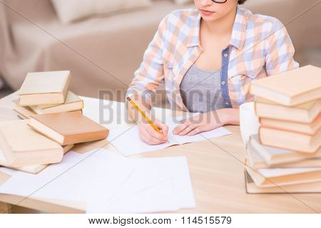 Young student girl is writing in her notebook.