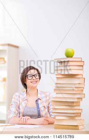 Girl looking at apple on top of books.
