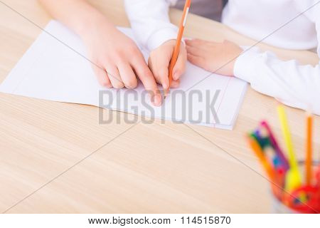 Young woman writing with little girl.