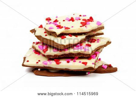 Chocolate bark with candy heart sprinkles stacked over white