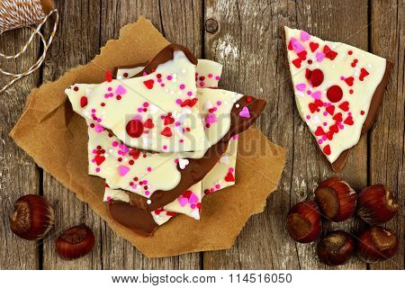 Chocolate bark with candy heart sprinkles over rustic wood