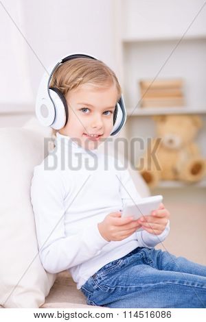 Little girl in headphones is sitting on the sofa.