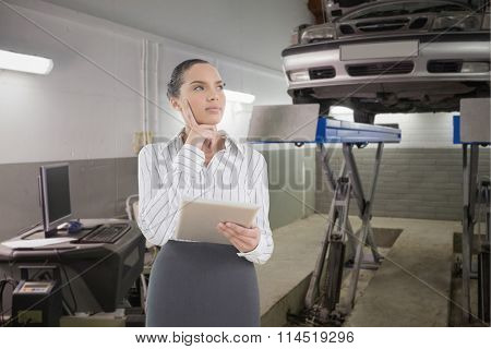 Confused businesswoman using a tablet pc against smiling mechanic standing next to a car