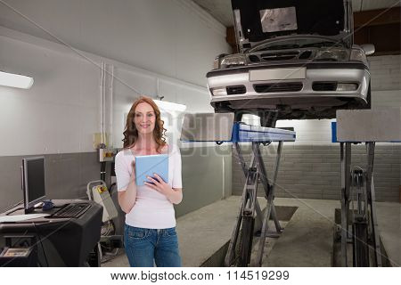 Pretty redhead using a tablet against smiling mechanicarms crossed next to a car on height