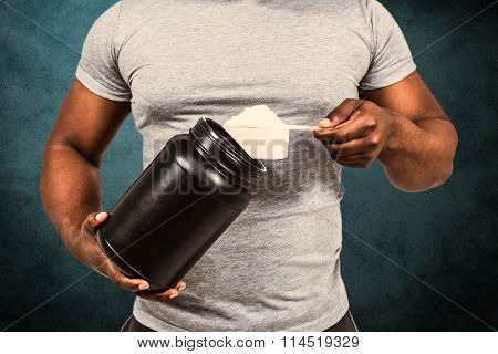 Fit man scooping protein powder against blue background
