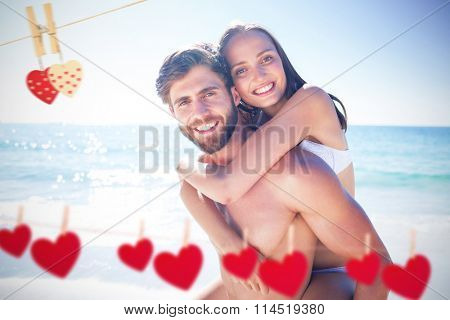 Handsome man giving piggy back to his girlfriend against hearts hanging on a line