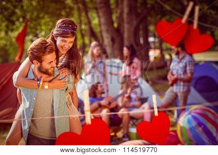 Hipster couple having fun on campsite against hearts hanging on a line