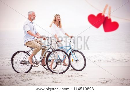 Happy couple cycling together against hearts hanging on a line