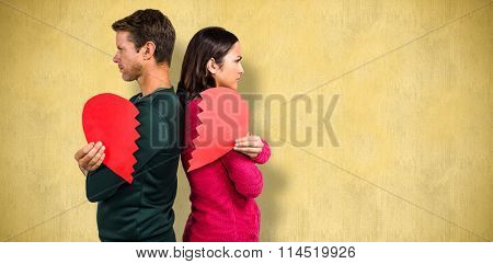 Serious couple standing back to back against orange background