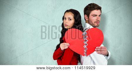 Couple back to back holding heart halves against blue background