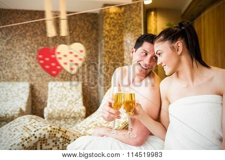 Couple relaxing in the thermal suite against hearts hanging on a line