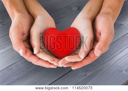 Couple holding miniature heart in hands against bleached wooden planks background