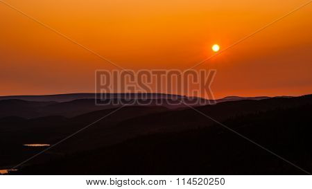 Setting Orange Sun Over Hills Receding Into Hazy Distance