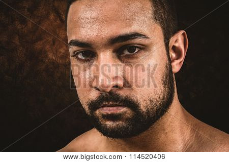 Muscular man frowning at camera against dark background