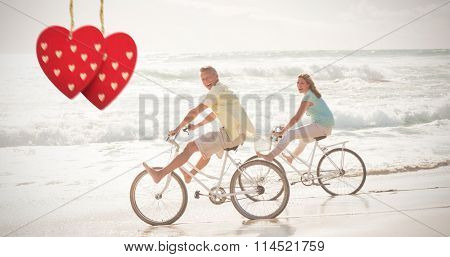 Happy couple on a bike ride against hearts hanging on a line
