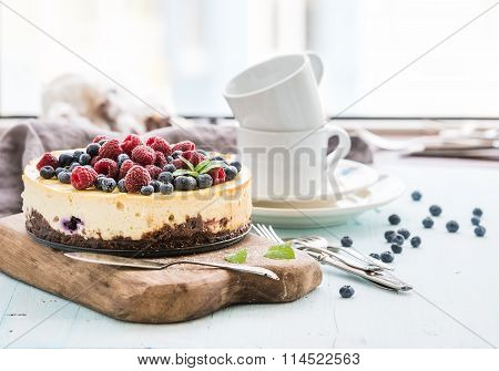 Cheesecake with fresh raspberries and blueberries on a wooden serving board, plates, cups, kitchen n