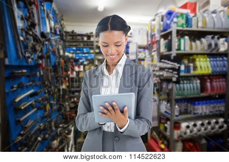 Businesswoman using a tablet with colleagues behind against full store room