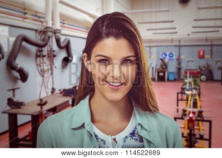 Pretty girl smiling against eqipments in factory