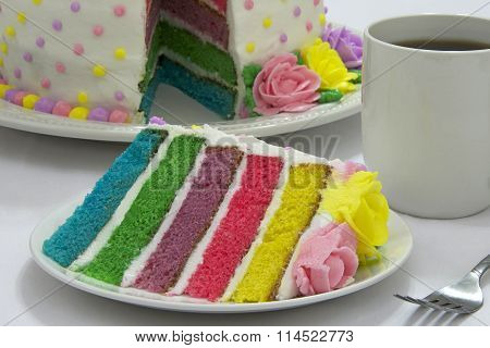 slice of rainbow layered cake on plate with whole cake in background with cup of coffee