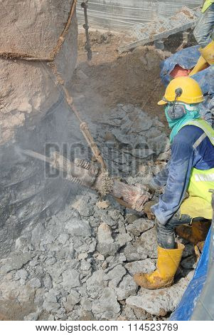 Construction workers using mobile concrete hacker at the construction site